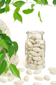 Herbal supplement pills and fresh leaves  – alternative medicine still life